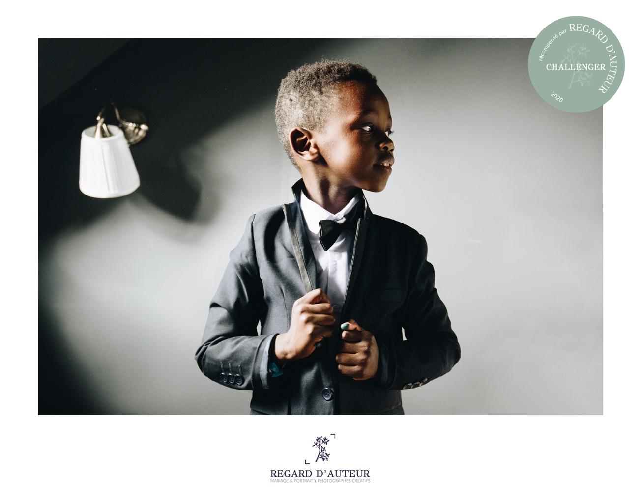 un jeune garçon s'habille pour célébrer le mariage de ses parents