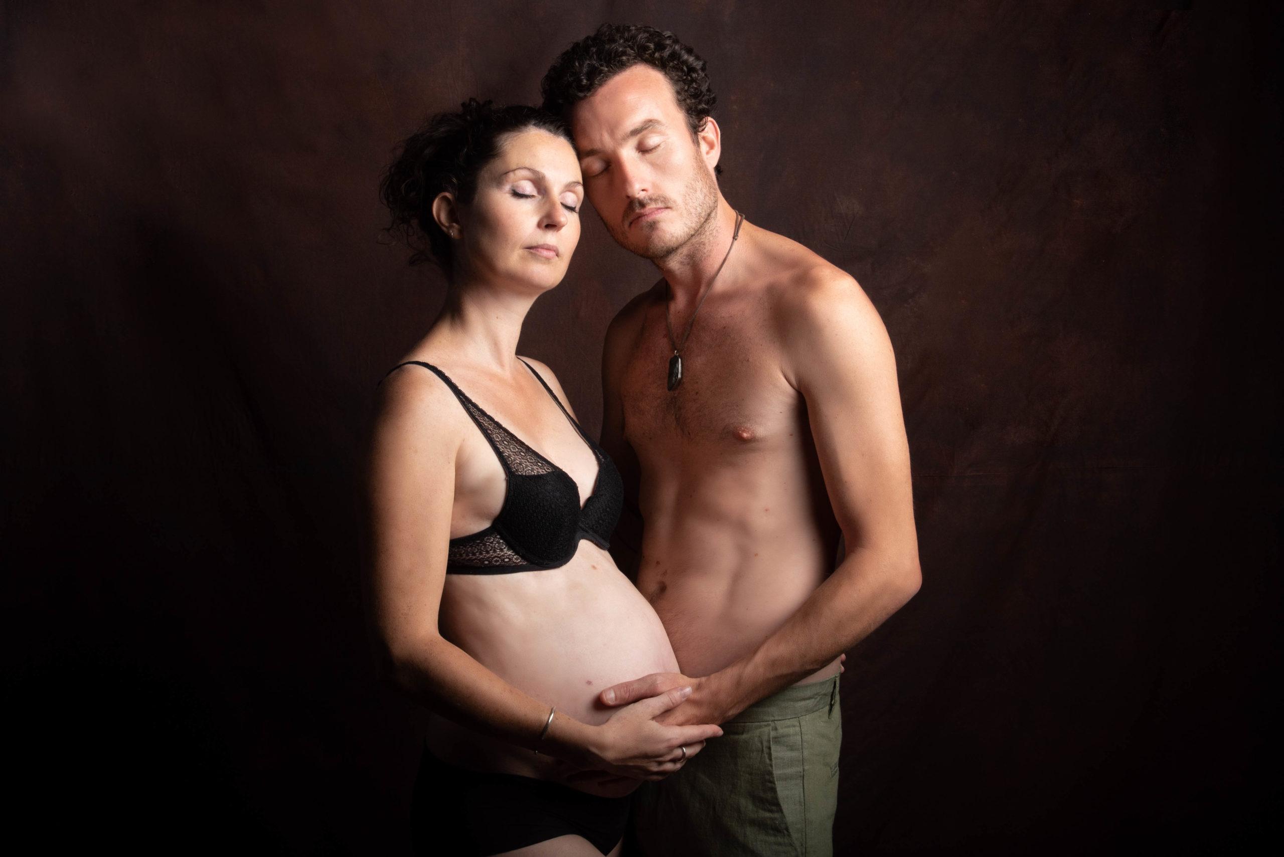 un joli couple, torse nu se connect l'un à l'autre pour une séance grossesse