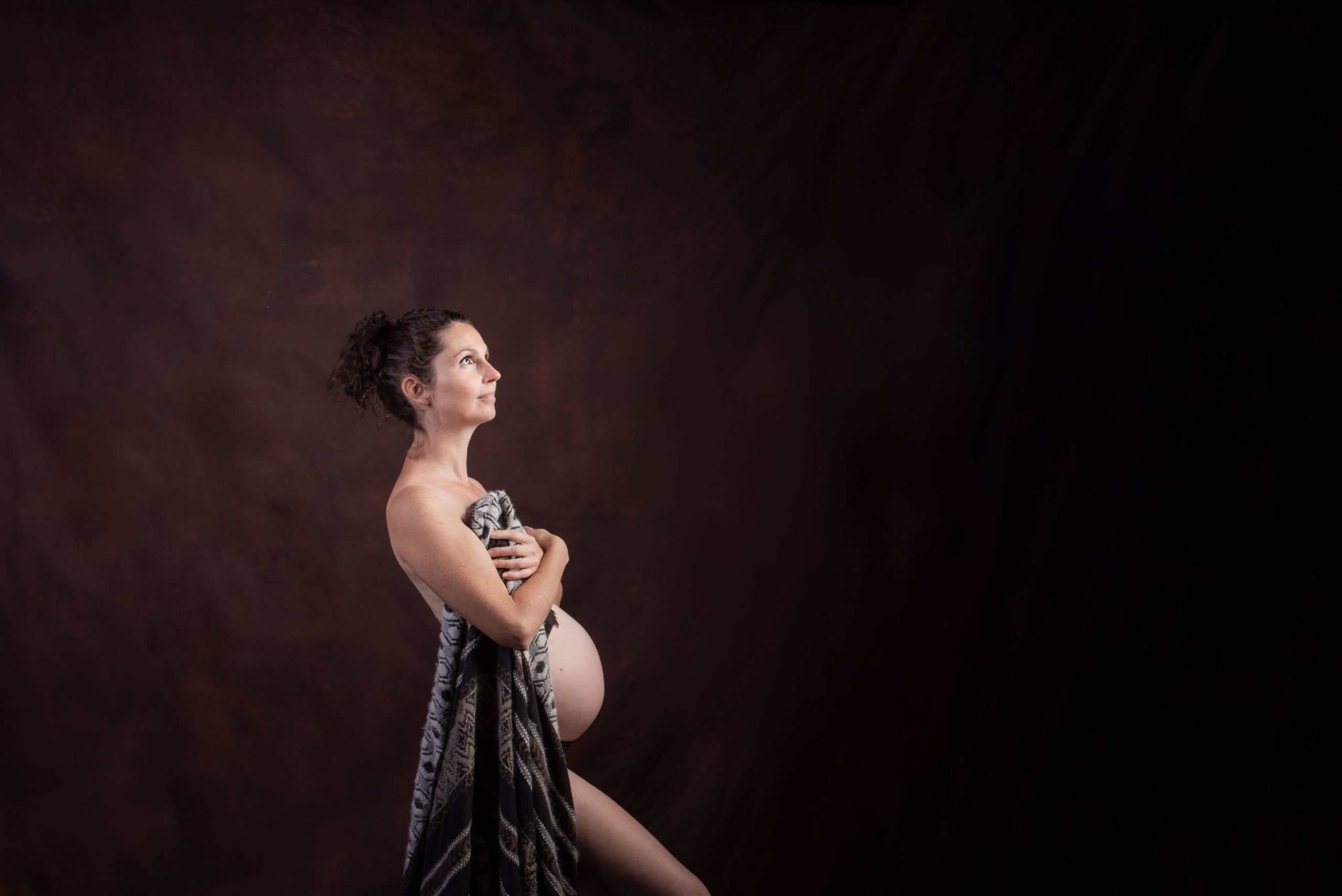 une femme enceinte pose en cachant sa poitrine avec une couverture