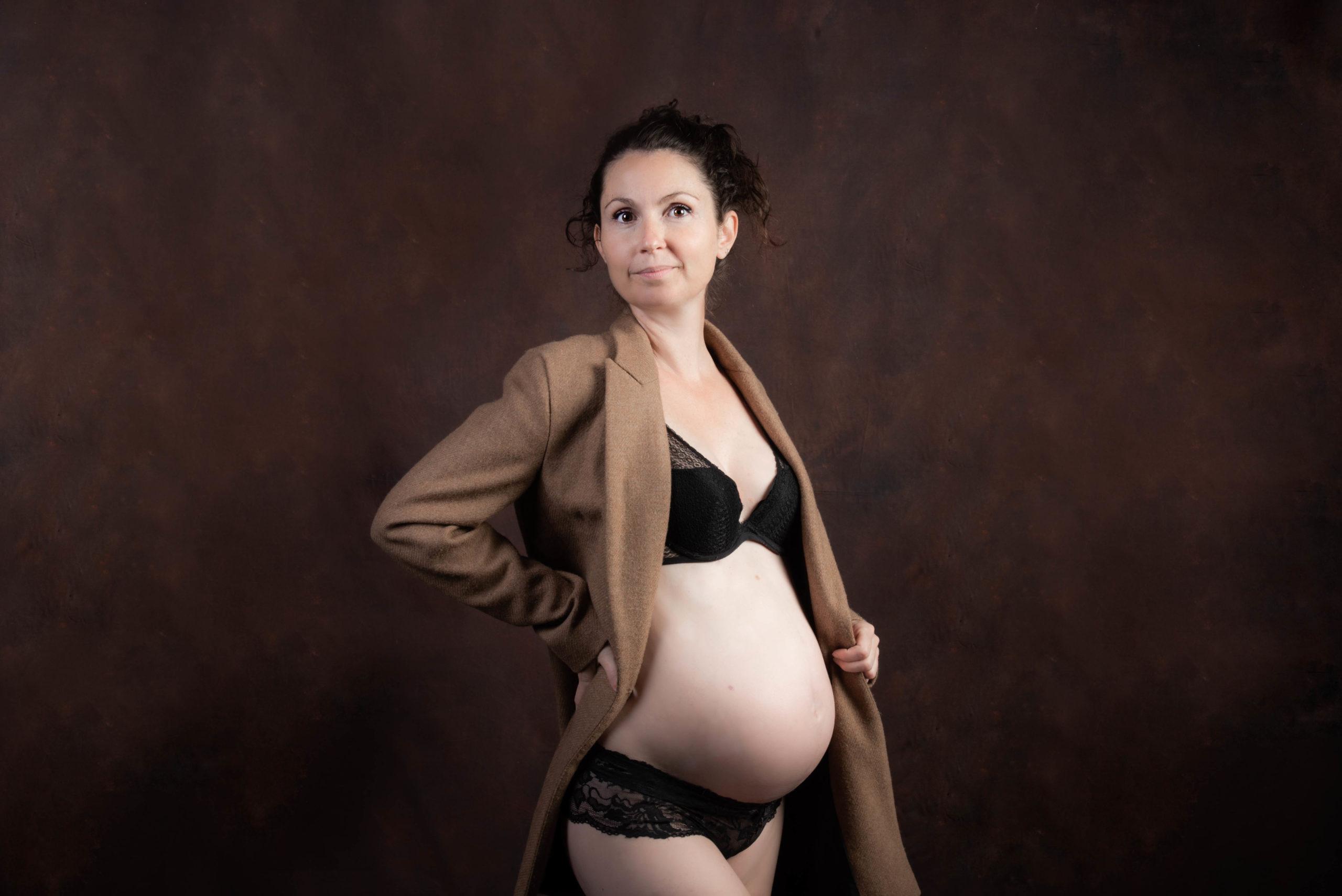 ue femme enceinte est vétue de son manteau