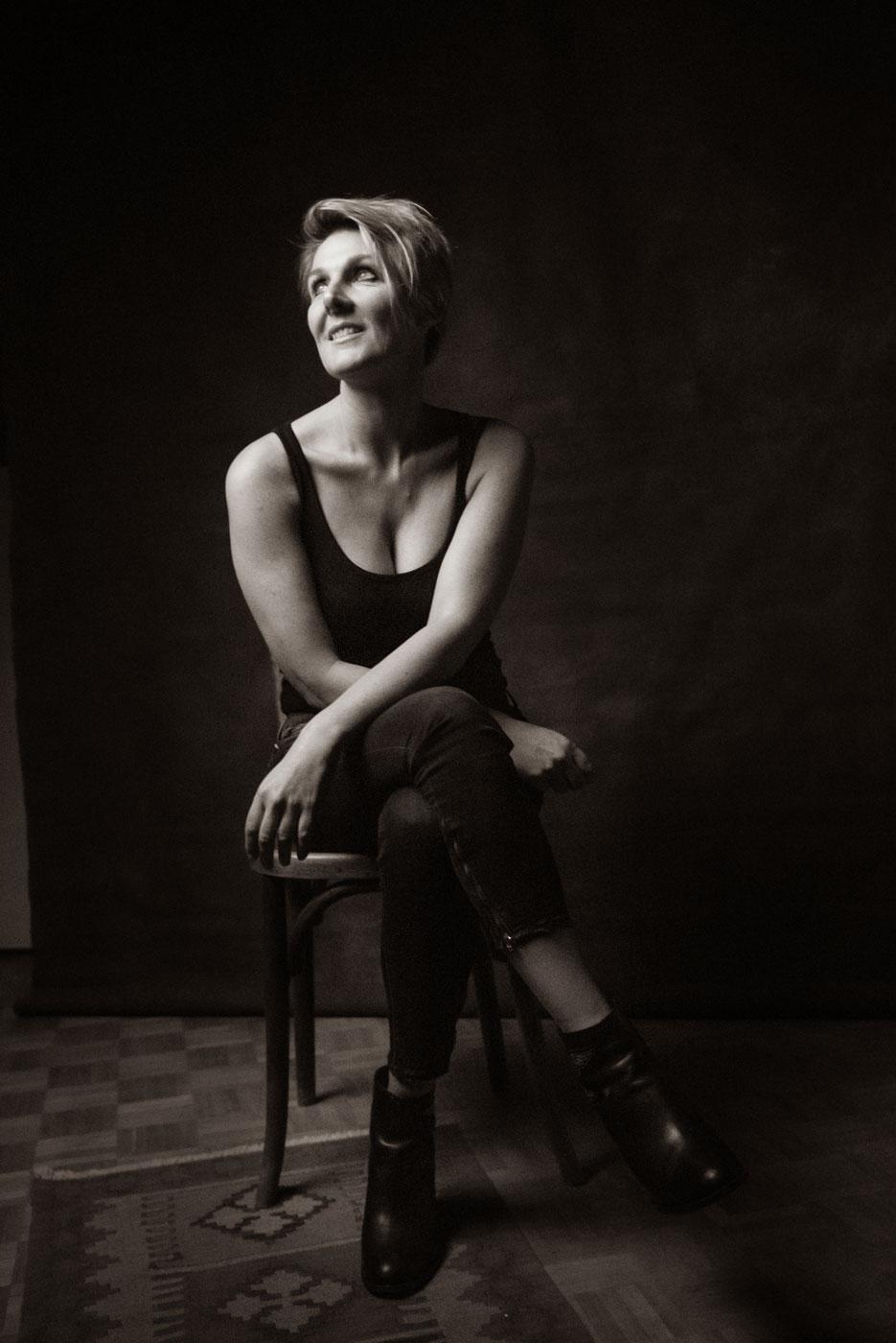 une femme souris et pose assise sur une chaise, séance portrait estime de soi, studio photo frederique jouvin rennes
