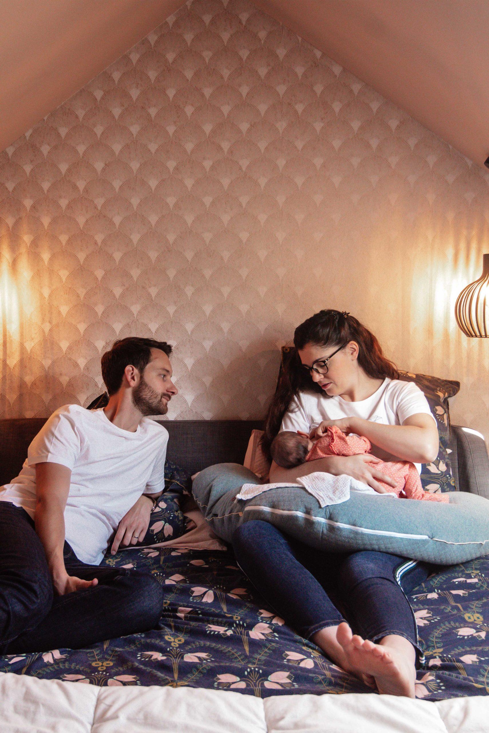 un couple pose lors d'une seance photo grossesse, lui dit un mot d'amour dans l'oreille