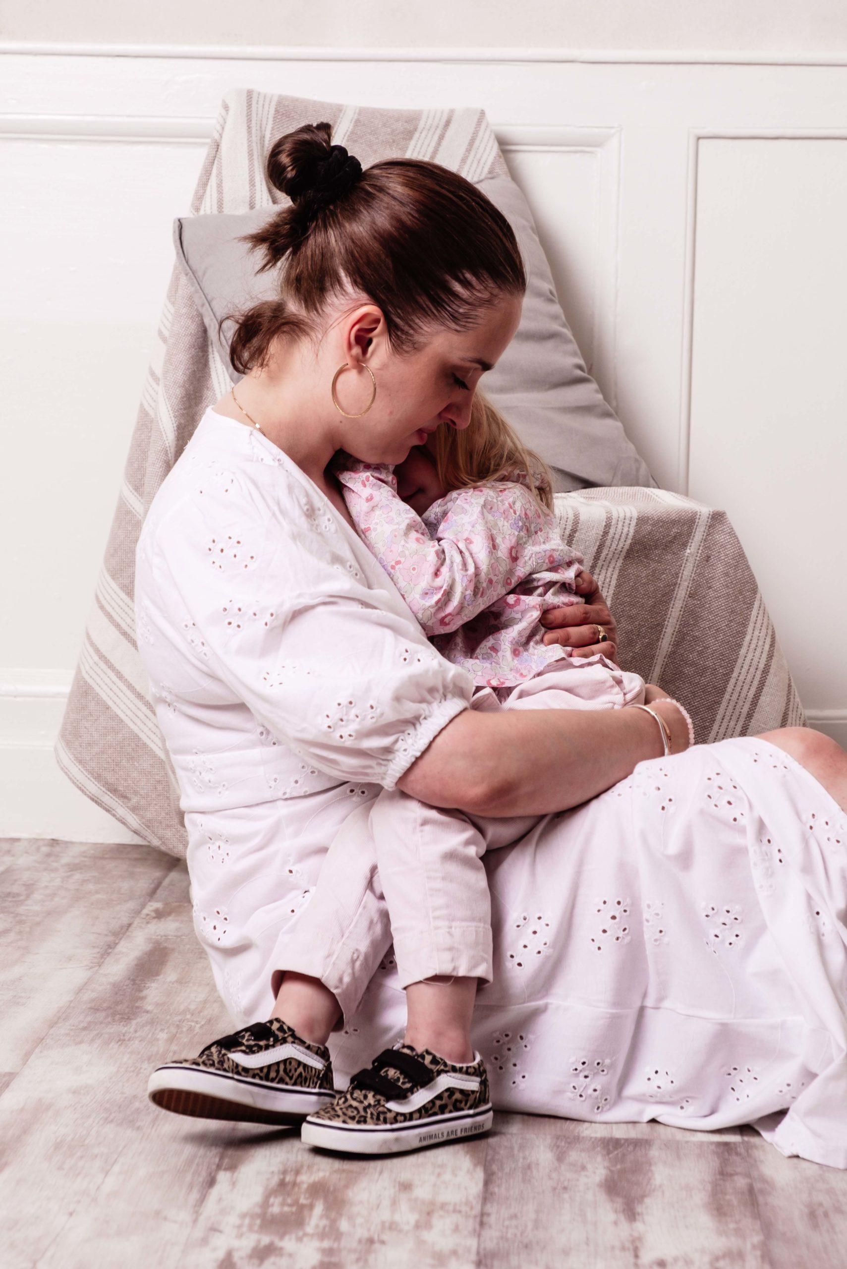 une mère tiens sa fille dans ses bras où elle se cache. seance famille a rennes