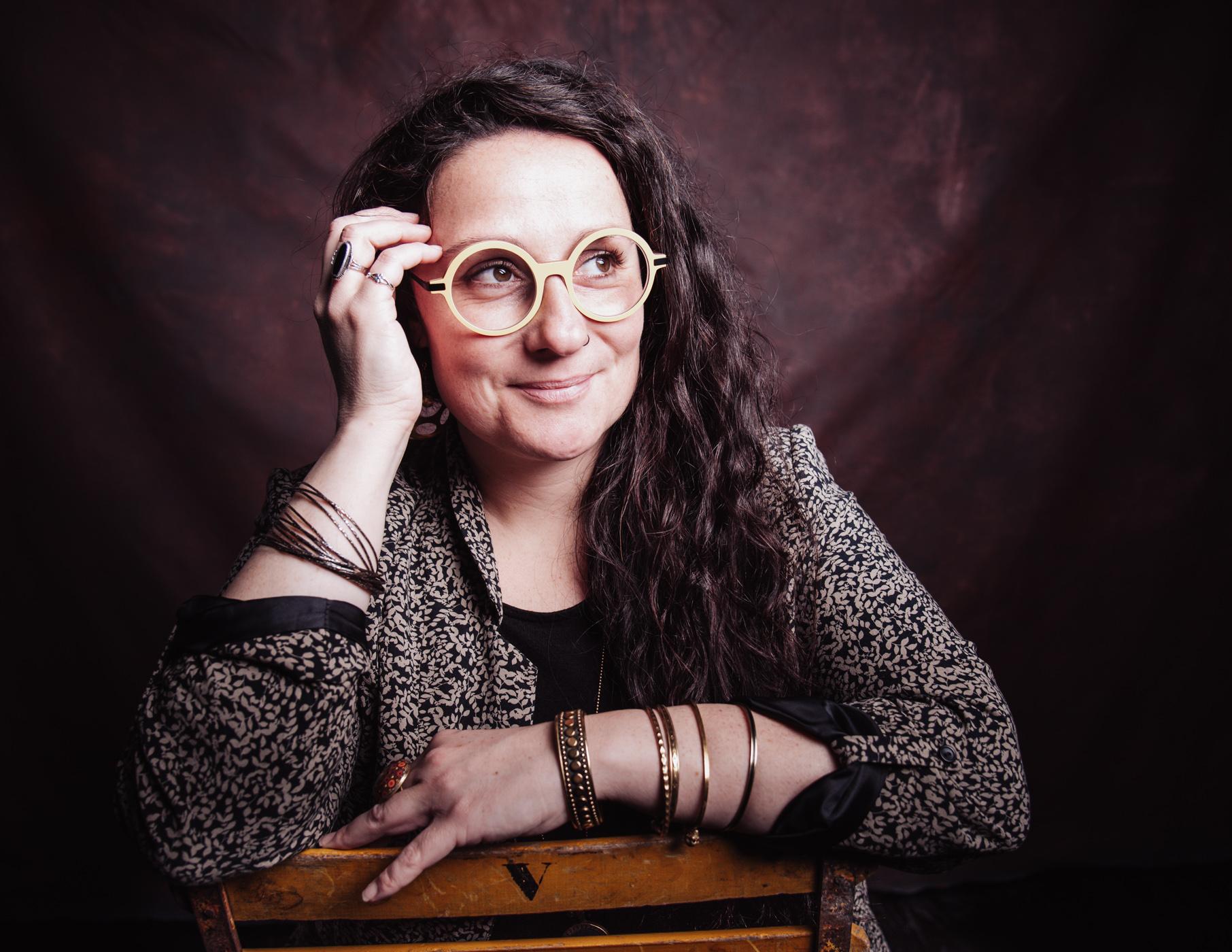 portrait d une femme avec des lunettes jaune assise sur une chaise jaune, studio rennes