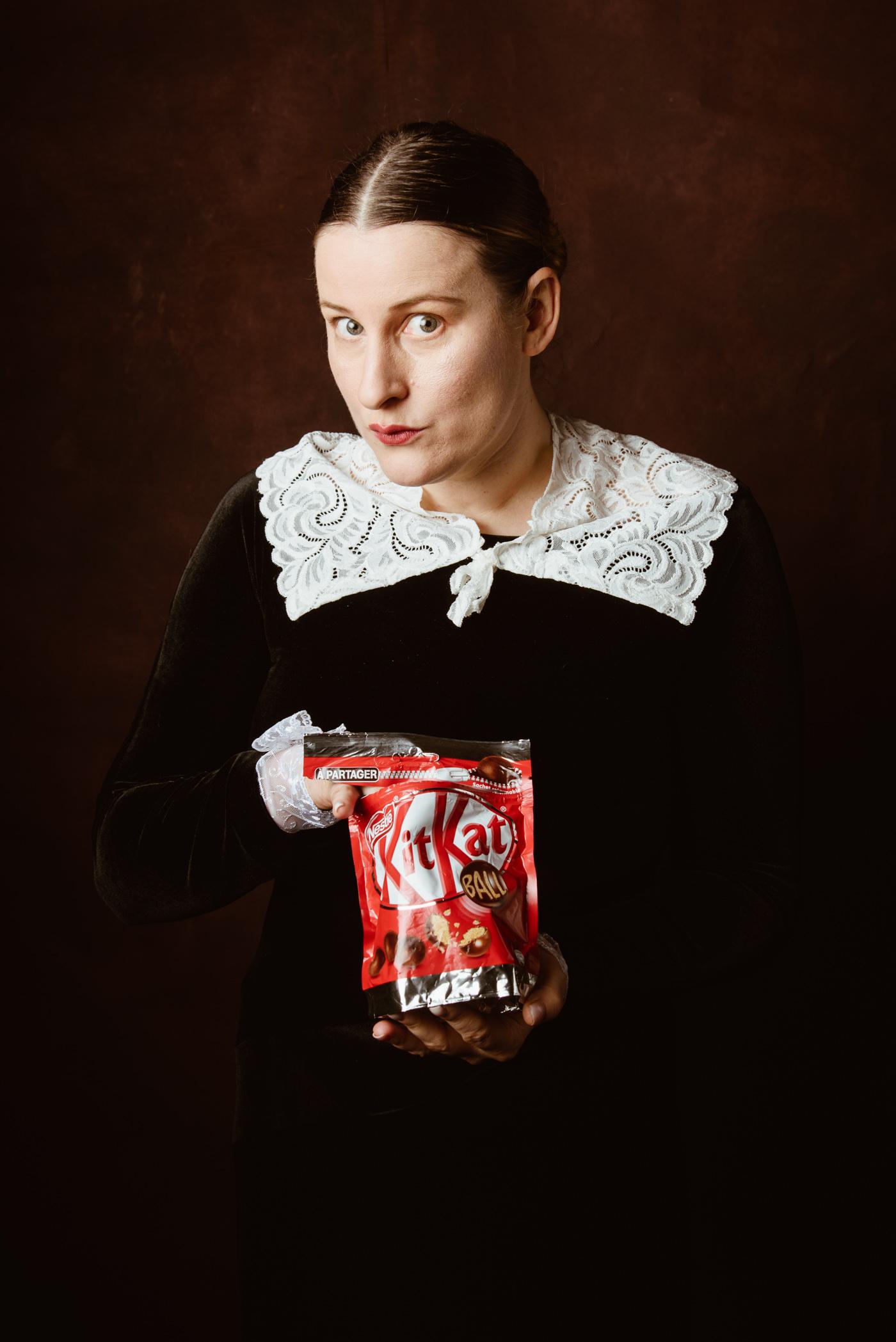 une femme de style renaissance mange des kit kat balls