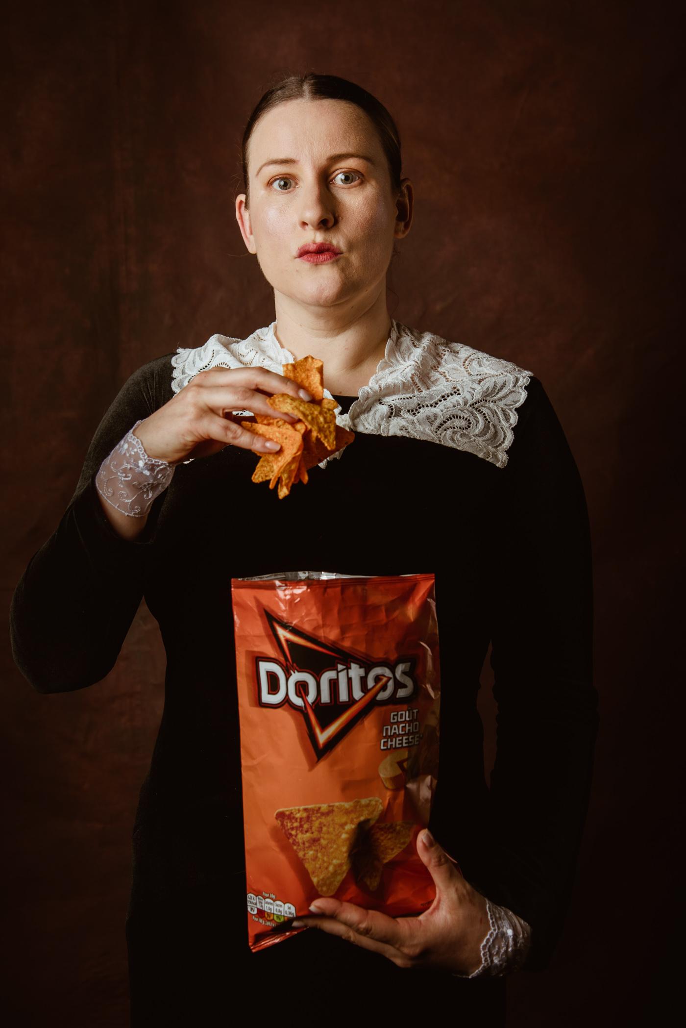 uen femme de style renaissance mange des doritos