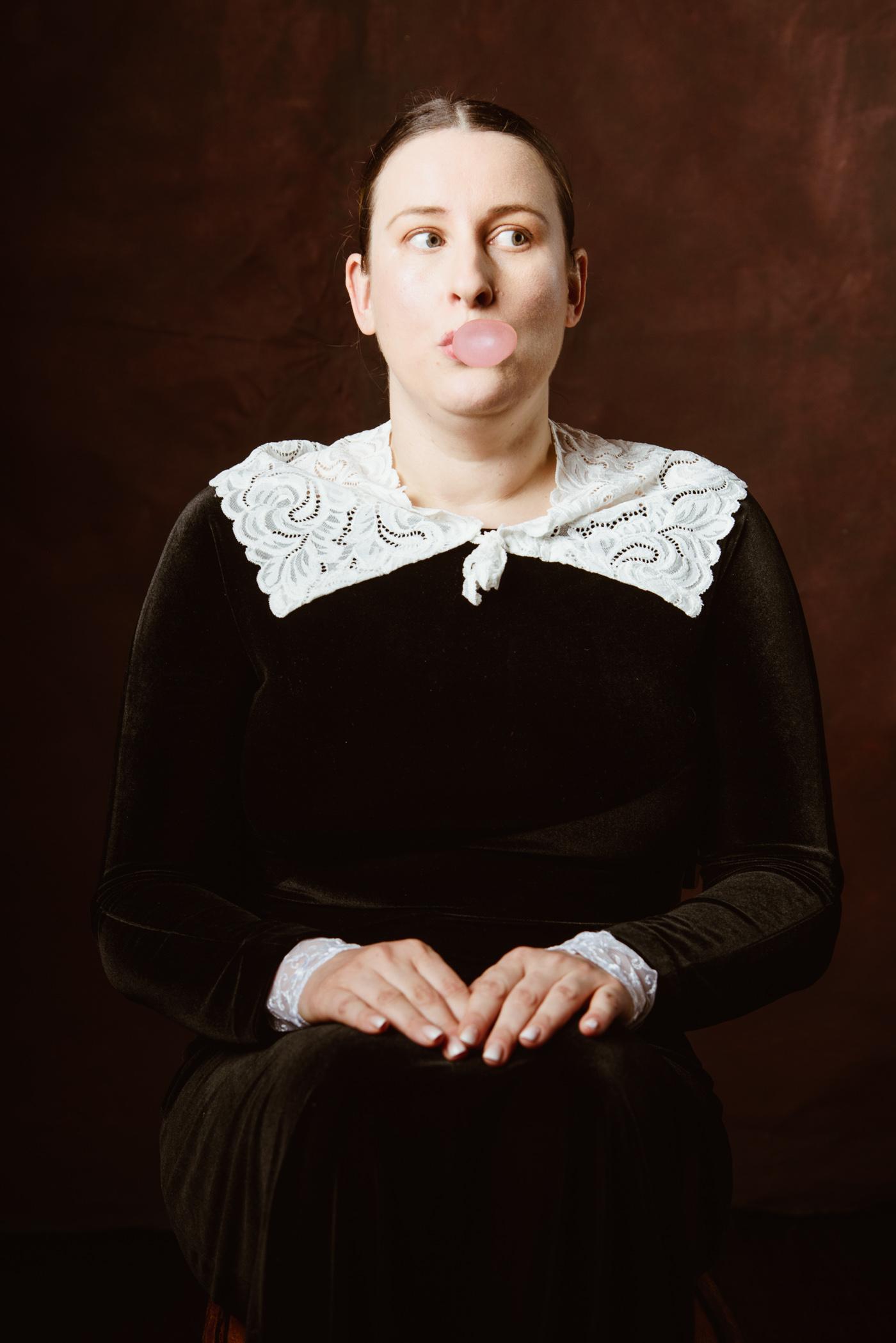 une femme pose en train de faire une bulle avec son chewing gum